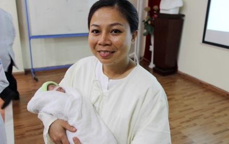 Người mẹ bế con trên tay trong sự nghẹn ngào, hạnh phúc