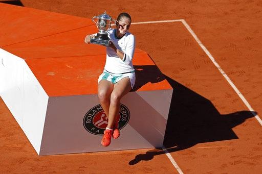 Khoảnh khắc Ostapenko ngồi trên bục chiến thắng để khoe chiếc cúp vô địch