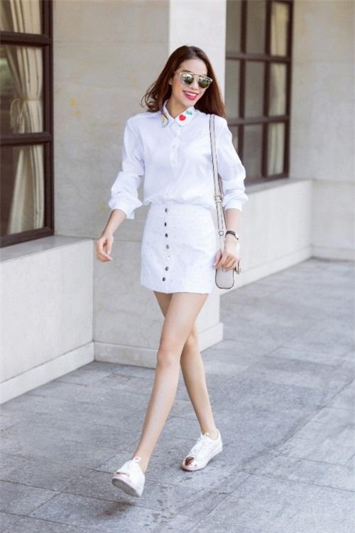 Phạm Hương trẻ trung với sơ mi trắng cùng chân váy trắng, túi xách trắng và giày trắng.
