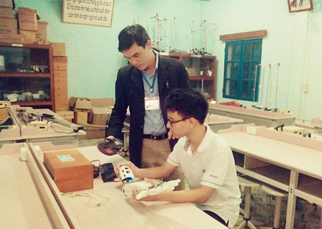 Thầy giáo Lê Công Long đang hướng dẫn học sinh Phạm Huy kiểm tra hoạt động của cánh tay Robot tại phòng thực hành của nhà trường.