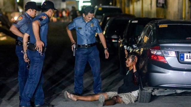 Một nghi phạm ma túy giơ tay xin hàng khi bị cảnh sát vây bắt tại Philippines (Ảnh: Al Jazeera)