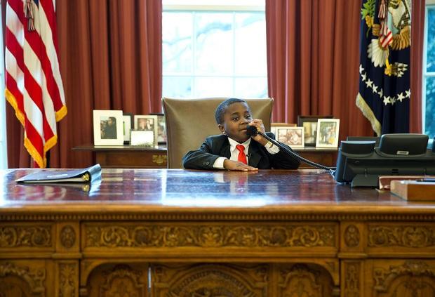 Một bé trai ngồi lên ghế của cựu Tổng thống Barack Obama khi ghé thăm Nhà Trắng năm 2013 (Ảnh: CBS)
