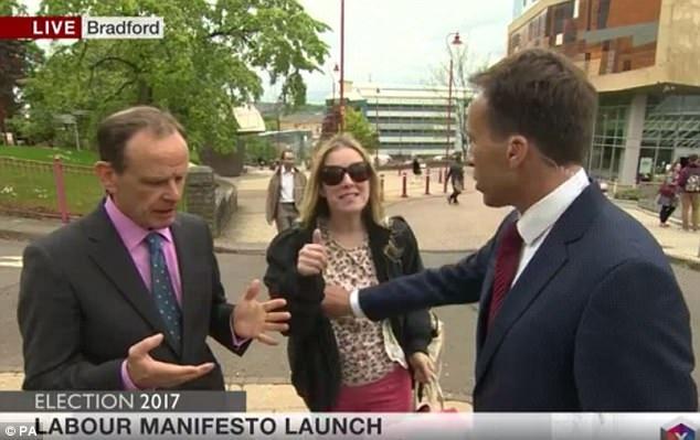 Phóng viên BBC vô tình chạm tay vào ngực phụ nữ qua đường khi tìm cách đẩy người này làm gián đoạn chương trình truyền hình trực tiếp. (Ảnh: BBC)