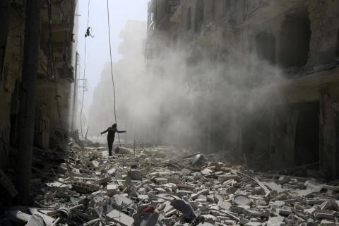 Một người đàn ông bước trên đống đổ nát sau cuộc không kích tại khu vực al-Qaterji bị quân nổi dậy chiếm đóng ở Aleppo ngày 25/9