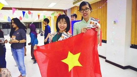 Phạm Thị Khánh Linh (bên trái) tự hào giới thiệu áo dài Việt trong buổi giao lưu văn hóa trên đất Thái.