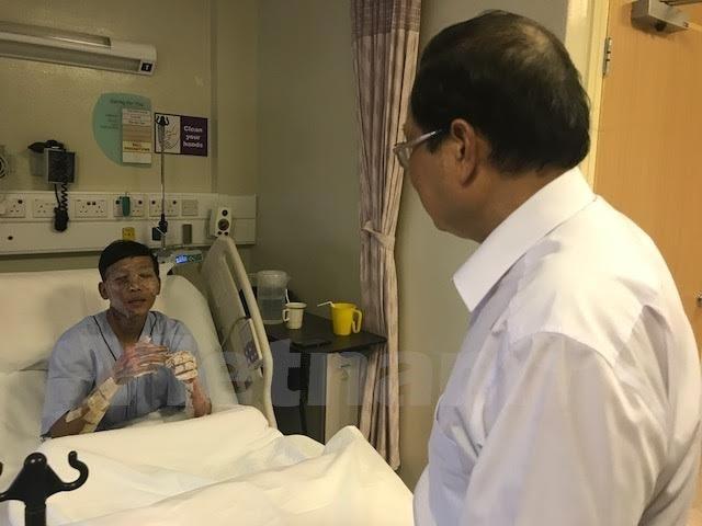 Đại sứ Việt Nam Nguyễn Tiến Minh thăm hỏi anh Phan Minh Dương, một trong ba thuyền viên gặp tai nạn khi đang làm việc trên tàu Le Tong Patriot, Singapore. (Ảnh: Mỹ Bình/Vietnam+)