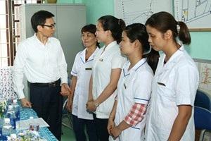 Phó Thủ tướng Vũ Đức Đam trò chuyện với các cán bộ trạm y tế xã Điện Thắng Trung. Ảnh: VGP/Đình Nam