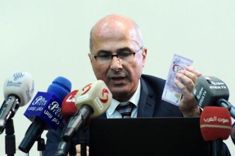 Thống đốc Ngân hàng Trung ương Syria cầm trên tay tờ 2.000 pound in hình Tổng thống Assad.