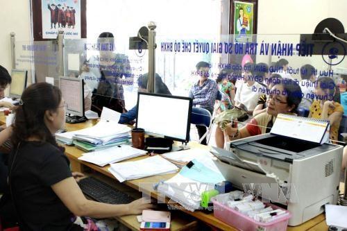 Giải quyết thủ tục về BHXH, BHYT tại Bảo hiểm xã hội quận Cầu Giấy. Ảnh: Dương Ngọc/TTXVN