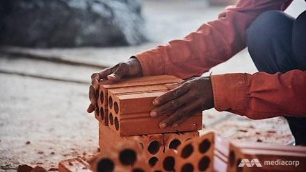 Xếp gạch, trộn bê tông, quét bụi, thậm chí vác vật liệu kim loại nặng... là những công việc mà những người phụ nữ ở công trường thực hiện. Ảnh: CNA