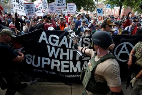 Những người biểu tình phản đối cuộc tuần hành Đoàn kết phe cánh hữu (Unite the Right) mang theo biểu ngữ chống lại tư tưởng coi da trắng là chủng tộc thượng đẳng. (Ảnh: Reuters)