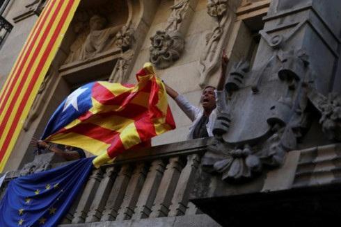 Một người biểu tình đem cờ ly khai lên ban công tòa nhà Bộ kinh tế của Catalonia. (ảnh: Reuters)