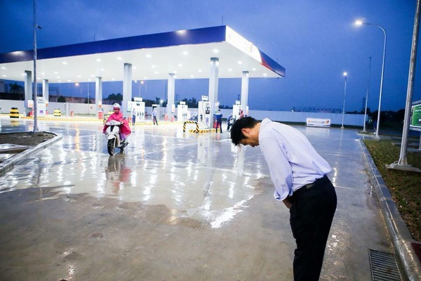Ông chủ trạm xăng Idemitsu Q8 đội mưa cúi đầu chào khách hàng.