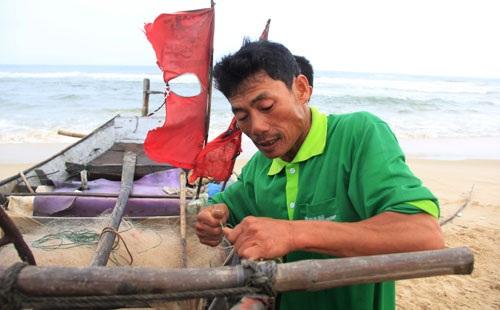 Ngư dân Bùi Văn Đoàn (trú xã Gio Hải) lên gân siết dây cước sửa lại con tàu 9CV cho chắc chắn để tiếp tục ra khơi (Ảnh: Ngọc Vũ)