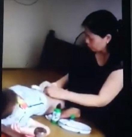 Bà Hiền tay không thực hiện nong tách bao quy đầu cho một bé trai. Ảnh cắt từ clip.