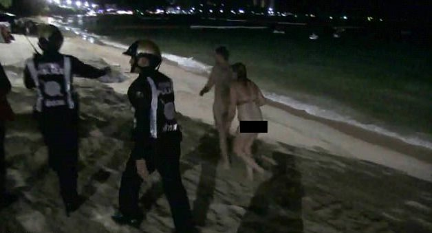 Cặp đôi bị áp giải dọc theo bãi biển
