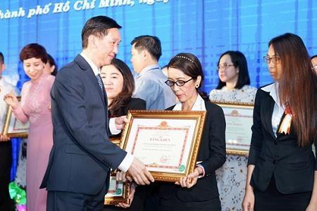 Ông Trần Vĩnh Tuyến - Phó chủ tịch UBND TP.HCM trao bằng khen của Bộ trưởng Bộ tài chính cho chị Trần Lê Hương đại diện công ty Nhựa Long Thành.