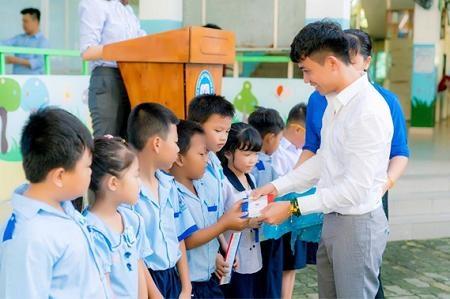 Ông Phạm Trần Nhật Minh trao các suất học bổng cho học sinh tiểu học.