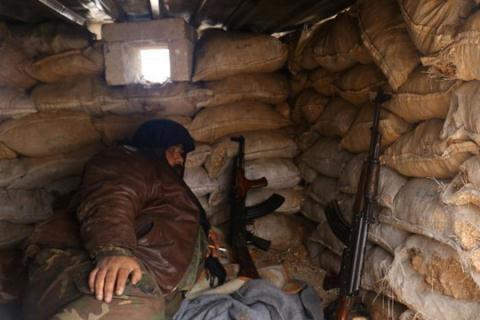 Một tay súng của phiến quân nghỉ ngơi ở khu vực Rashideen, tỉnh Aleppo, Syria hôm 30/12. Ảnh: Reuters