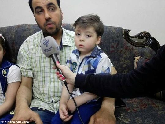 Bé Omran ngồi trên đùi cha mình. Ảnh: Daily Mail