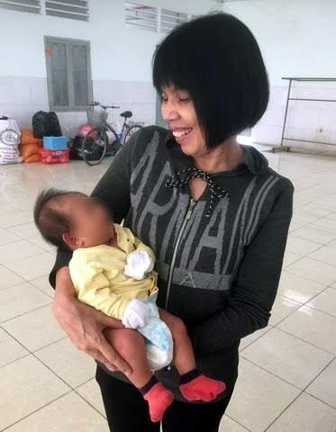 Chị Căn, người phụ trách nhà tạm lánh, bế một em bé. Mẹ bé người Ninh Bình vào tạm lánh sau khi chồng bỏ đi vì bệnh ung thư.