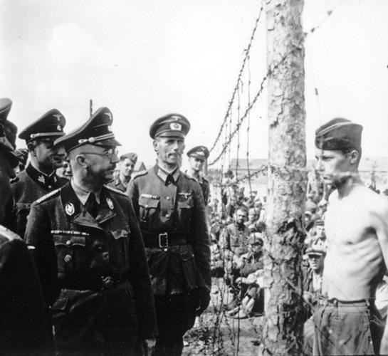 Binh sĩ Anh (cởi trần) nhìn thẳng vào mặt trùm mật vụ phát xít Heinrich Himmler khi hắn đi thị sát một nhà tù. Ảnh: AP