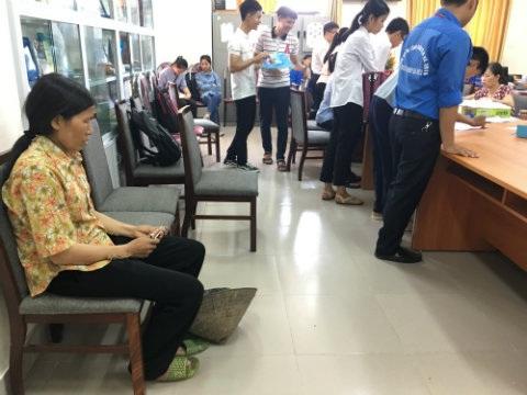Bà Nguyễn Thị Thêm, mẹ của Ngọc Tuấn, đi dép tổ ong cũ, đội nón rách, mân mê từng đồng tiền để chuẩn bị đóng học cho con. Ảnh: Thế Anh