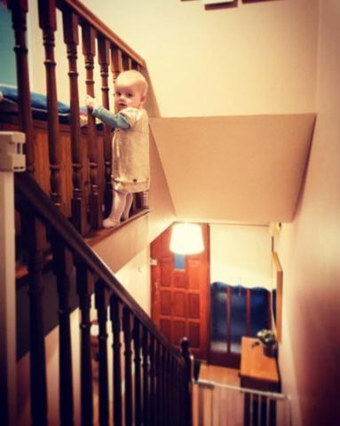 Cô bé vô tư trèo ra phía ngoài lan can cầu thang