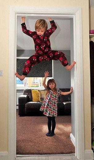 Cậu bé 6 tuổi trèo lên cửa trong khi chị gái Sienna đứng phía dưới