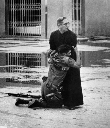 Cha Luis Manuel Padilla ôm một binh sĩ quân chính phủ Venezuela bị thương tên đường phố Puerto Cabello vào tháng 6/1962. Bức ảnh này đã đem lại giải Putlizer cho tác giả Hector Rondon. Ảnh: AP