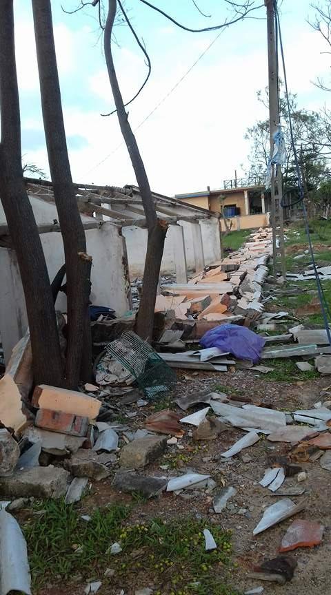 Con đường dẫn vào trường lổn nhổn gạch, mái của các ngôi nhà sau khi bão quét qua.