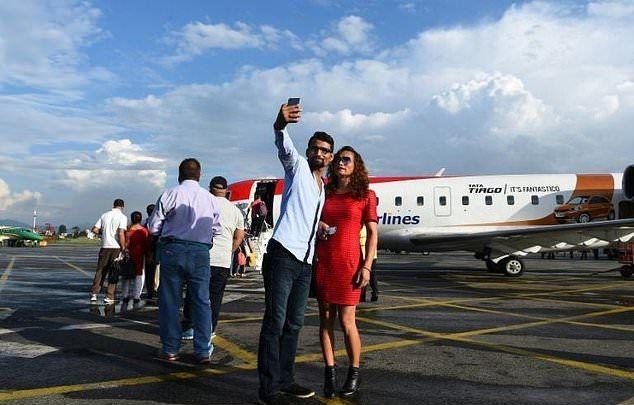 Cặp đôi chụp ảnh ở phi trường trước khi lên máy bay