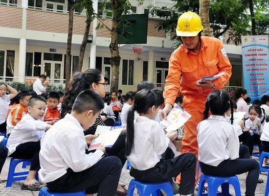 Công nhân EVN Hà Nội phát tờ rơi cách thức sử dụng điện an toàn tiết kiệm tới học sinh trường tiểu học Nghĩa Tân.