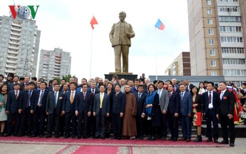Các đại biểu và bà con người Việt tự hào đứng dưới bức tượng Bác Hồ mới khánh thành tại Ulyanovsk.
