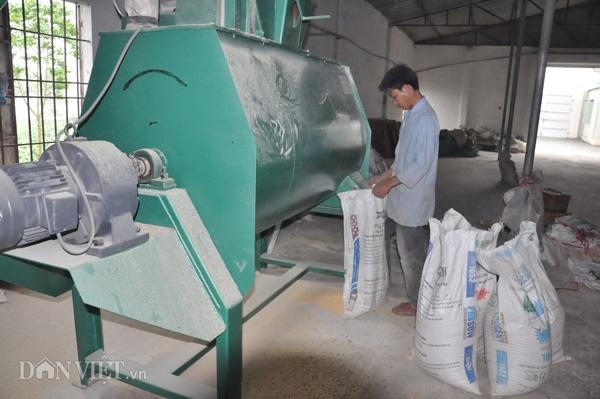 Công nhân sản xuất cám phục vụ đàn lợn tại trang trại của ông Long ở huyện Thanh Oai (Hà Nội).
