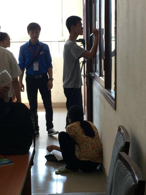 Nguyễn Ngọc Tuấn hí húi viết hồ sơ nhập học, còn người mẹ liên tục ngửa cổ ngóng con. Ảnh: Thế Anh