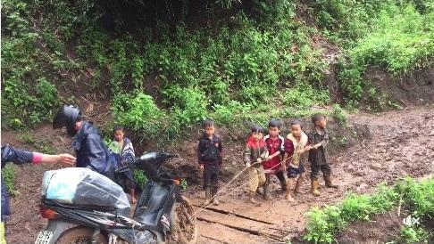 Các trò dốc sức kéo chiếc xe đã dính đầy bùn đất của thầy lên dốc trơn.