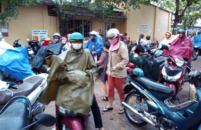 Phụ huynh ở Sóc Trăng đội mưa đưa con đến trường học sáng ngày 27/12.