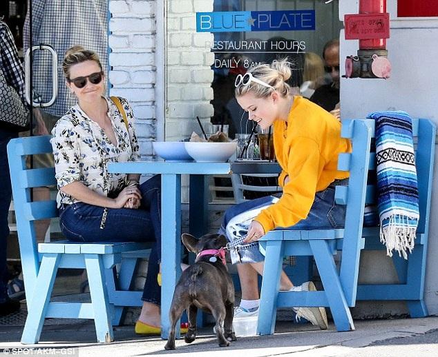 Ava còn cưng nựng chú cún cưng của gia đình trong lúc ăn xong bữa trưa. Reese mỉm cười khi bắt gặp giới săn tin đang chụp hình mẹ con cô.