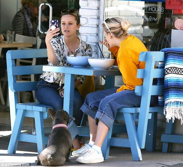 Ngôi sao 40 tuổi hầu như không trang điểm, vừa dùng bữa vừa trò chuyện với con gái trong lúc kiểm tra điện thoại.