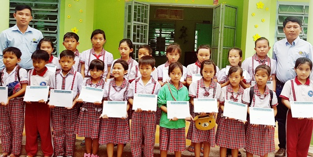 Đại diện Công ty Grobest tại Sóc Trăng trao học bổng cho học sinh Trường Tiểu học thị trấn Cù Lao Dung (huyện Cù Lao Dung).