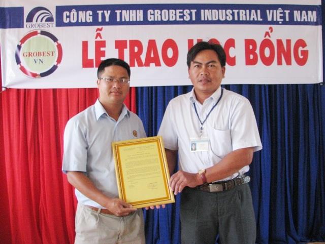 Thầy Lâm Vũ Lam- Hiệu trưởng Trường Tiểu học Vĩnh Phước 1 (phải) trao Thư cám ơn đến ông Đinh Xuân Lâm- đại diện các nhà tài trợ học bổng.