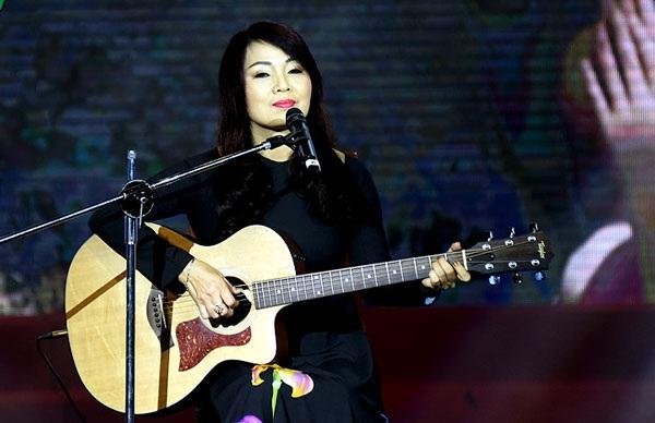 """NSND Thái Bảo ôm đàn guitar thể hiện ca khúc """"Vết chân tròn trên cát"""" của nhạc sĩ Trần Tiến (Ảnh: Nguyễn Hùng)."""