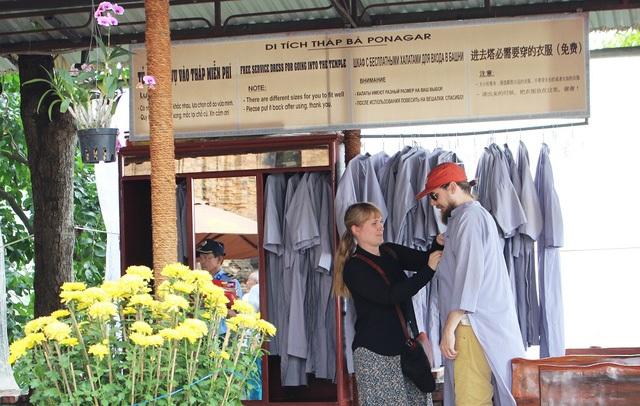 Du khách nước ngoài hào hứng khoác áo dài khi vào tham quan Tháp bà Ponagar ở Nha Trang. Ảnh: D.T