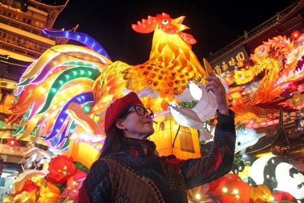Một phụ nữ chụp ảnh cùng đèn lồng có hình gà trống tại thành phố Thượng Hải, Trung Quốc (Ảnh: China Daily)