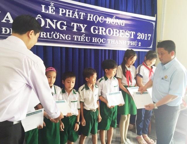 Ông Tăng Văn Hoa- Giám đốc Công ty Grobest Việt Nam tại Cà Mau (phải) trao học bổng cho các em học sinh Trường Tiểu học Thạnh Phú 2 (xã Thạnh Phú, huyện Cái Nước).