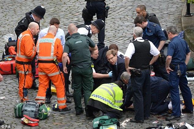 Nghị sĩ Tobias Ellwood (giữa) trợ giúp nhóm cứu hộ tại hiện trường (Ảnh: AP)