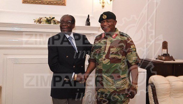 Tổng thống Zimbabwe Robert Mugabe tươi cười bắt tay Tổng tham mưu trưởng quân đội Constantino Chiwenga sau khi bị quản thúc. (Ảnh: Getty)