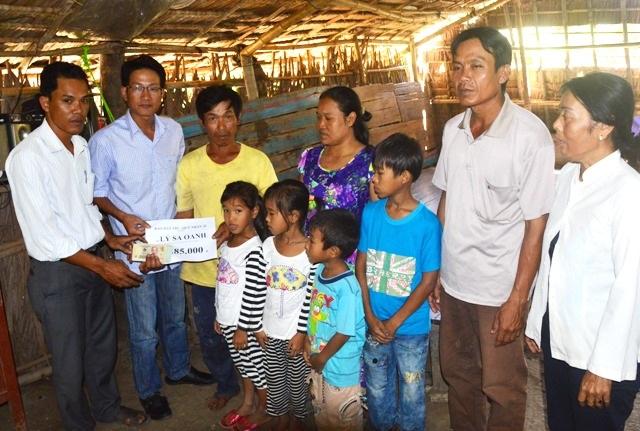 PV Dân trí cùng đại diện UBND xã Trường Khánh trao tiền bạn đọc đến gia đình anh Lý Sa Oanh.
