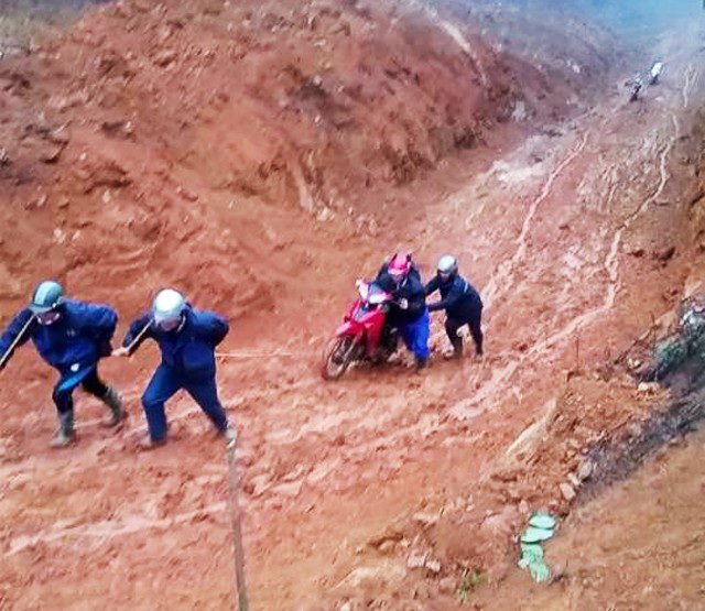 Những đoạn dốc cao vào ngày mưa là nỗi ám ảnh của các thầy giáo Trường Tiểu học Tri Lễ 4. Để đưa xe vượt qua con dốc trơn trượt, lầy lội phải có sự hợp sức của 5 người (ảnh Nguyễn Hiệp)